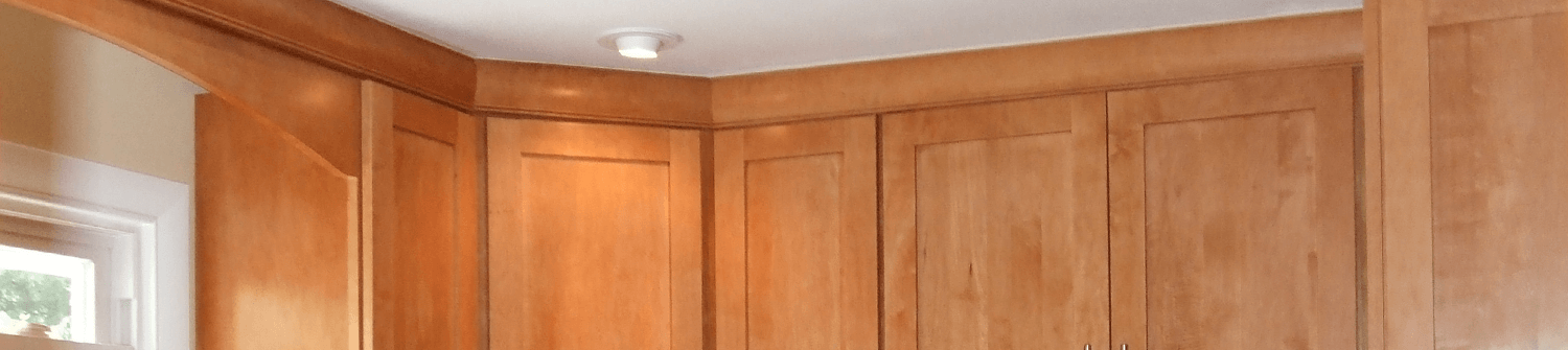 solid oak kitchen cabinets that reach the ceiling with accent lighting